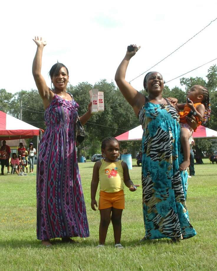 Beaumont residents Quintella Hawkins and Catherine Hawkins and children enjoyed live music at a back-to-school family event Saturday in Magnolia Park. Photo: Sarah Moore