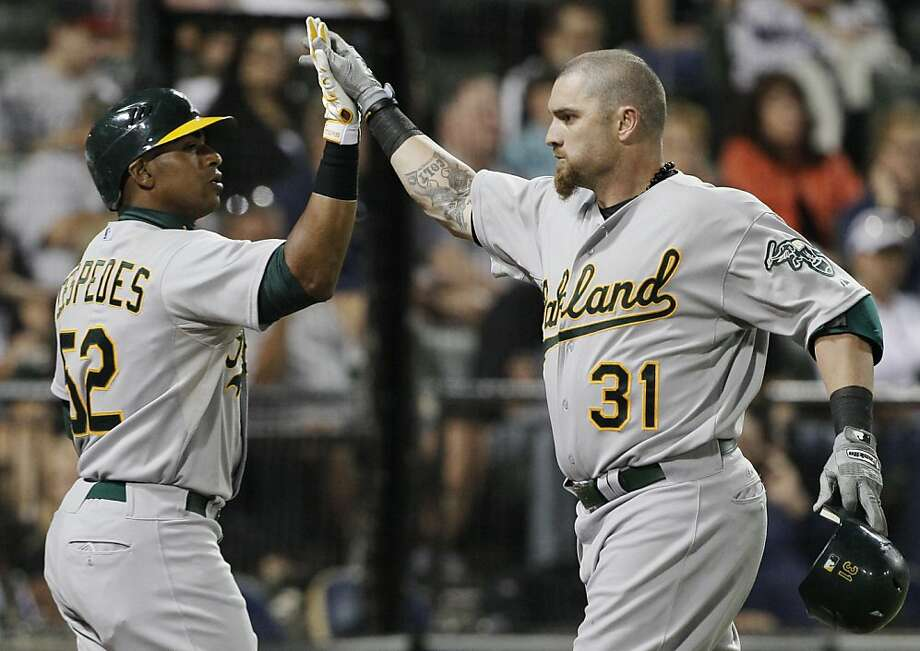 Oakland Athletics' Jonny Gomes, right, celebrates with Yoenis Cespedes after hitting a solo home run against the Chicago White Sox during the eighth inning of a baseball game in Chicago, Saturday, Aug. 11, 2012. (AP Photo/Nam Y. Huh) Photo: Nam Y. Huh, Associated Press