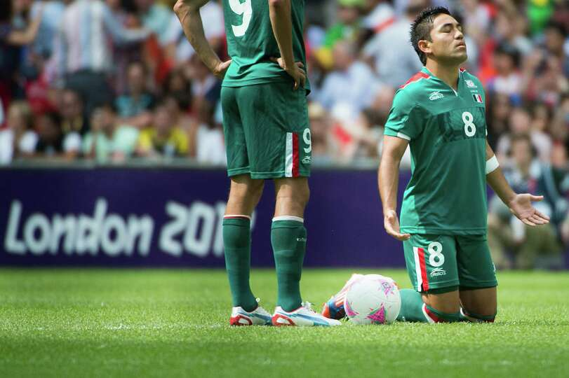Mexico's Marco Fabian kneels at the center of the pitch before facing Brazil in the men's soccer gol