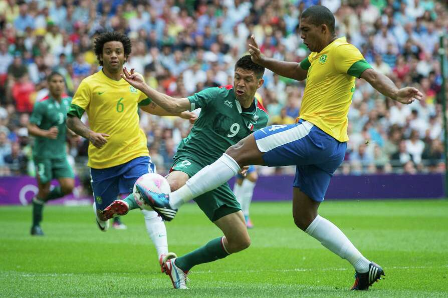 Mexico's Oribe Peralta challenges for a ball against Brazil's Juan Jesus during the men's soccer gol