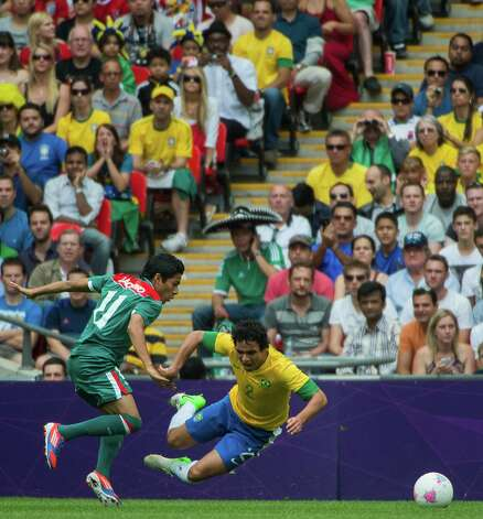 Brazil's Rafael takes spill as Mexico's Javier Aquino defends during the men's soccer gold medal match at the 2012 Summer Olympics on Saturday, Aug. 11, 2012, in London. Photo: Smiley N. Pool, Houston Chronicle / © 2012  Houston Chronicle