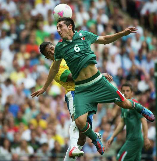 Mexico's Hector Herrera wins a header from Brazil's Alex Sandro during the men's soccer gold medal m