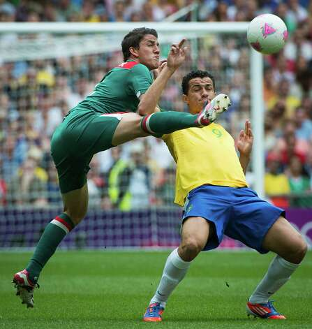 Mexico's Hiram Mier, left, tries to keep the bal from Brazil's Leandro Damiao during the men's soccer gold medal match at the 2012 Summer Olympics on Saturday, Aug. 11, 2012, in London. Photo: Smiley N. Pool, Houston Chronicle / © 2012  Houston Chronicle