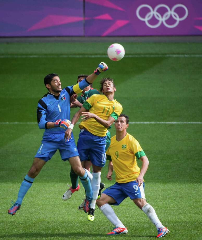 Mexico goalkeeper Jose Corona punches a ball away from Brazil's Neymar during the men's soccer gold medal match at the 2012 Summer Olympics on Saturday, Aug. 11, 2012, in London. Photo: Smiley N. Pool, Houston Chronicle / © 2012  Houston Chronicle