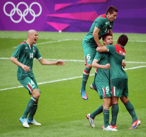 Mexico's Oribe Peralta (9) celebrates with Marco Fabian (8), Hector Herrera (6) and Jorge Enriquez (14) after he scored a goal in the 75th minute against Brazil in the men's soccer gold medal match at the 2012 Summer Olympics on Saturday, Aug. 11, 2012, in London. Photo: Smiley N. Pool, Houston Chronicle / © 2012  Houston Chronicle