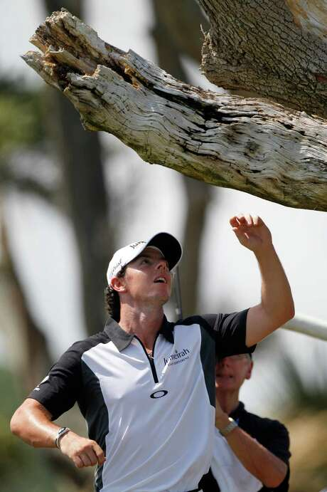 After removing his tee shot from a tree, Rory McIlroy parred the hole en route to a 32 on the front nine and a share of the lead in the abbreviated round. Photo: Evan Vucci / AP