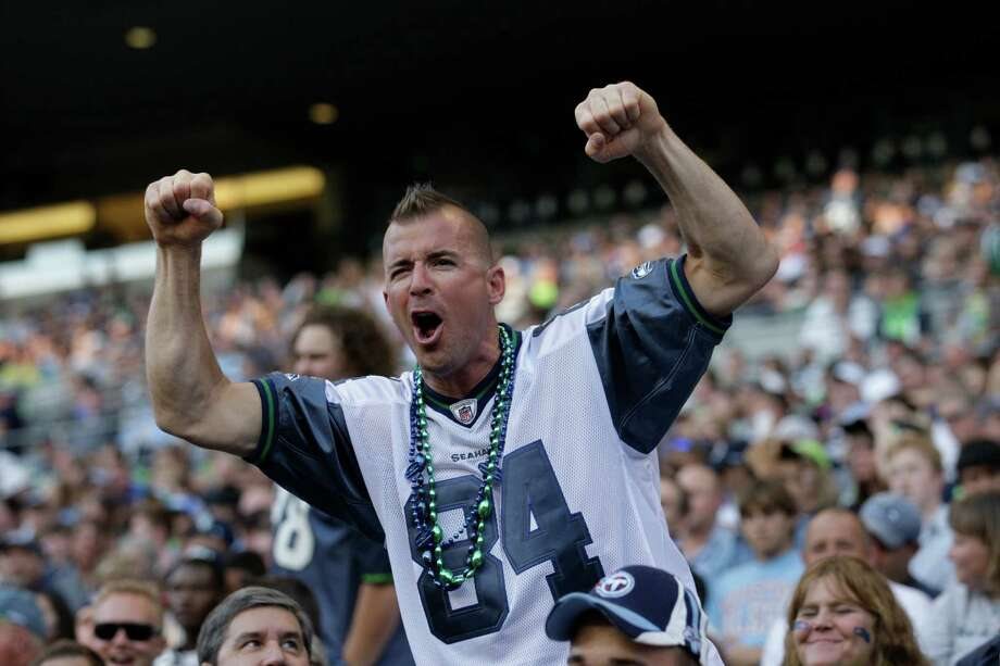 A Seattle Seahawks fan cheers during the first half of an NFL football preseason game against the Tennessee Titans on Saturday. Photo: Ap