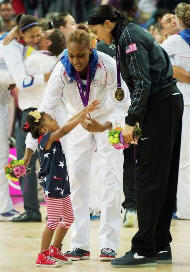 Lailaa Williams, 3, reaches up to her mother,  Candace Parker of the USA and France's Sandrine Gruda