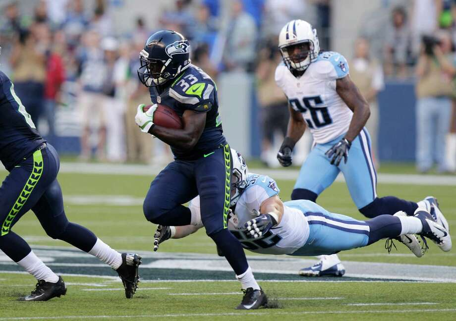 Tennessee Titans Colin McCarthy (52) dives to tackle Seattle Seahawks Leon Washington (33) in the first half Saturday. Photo: Ap