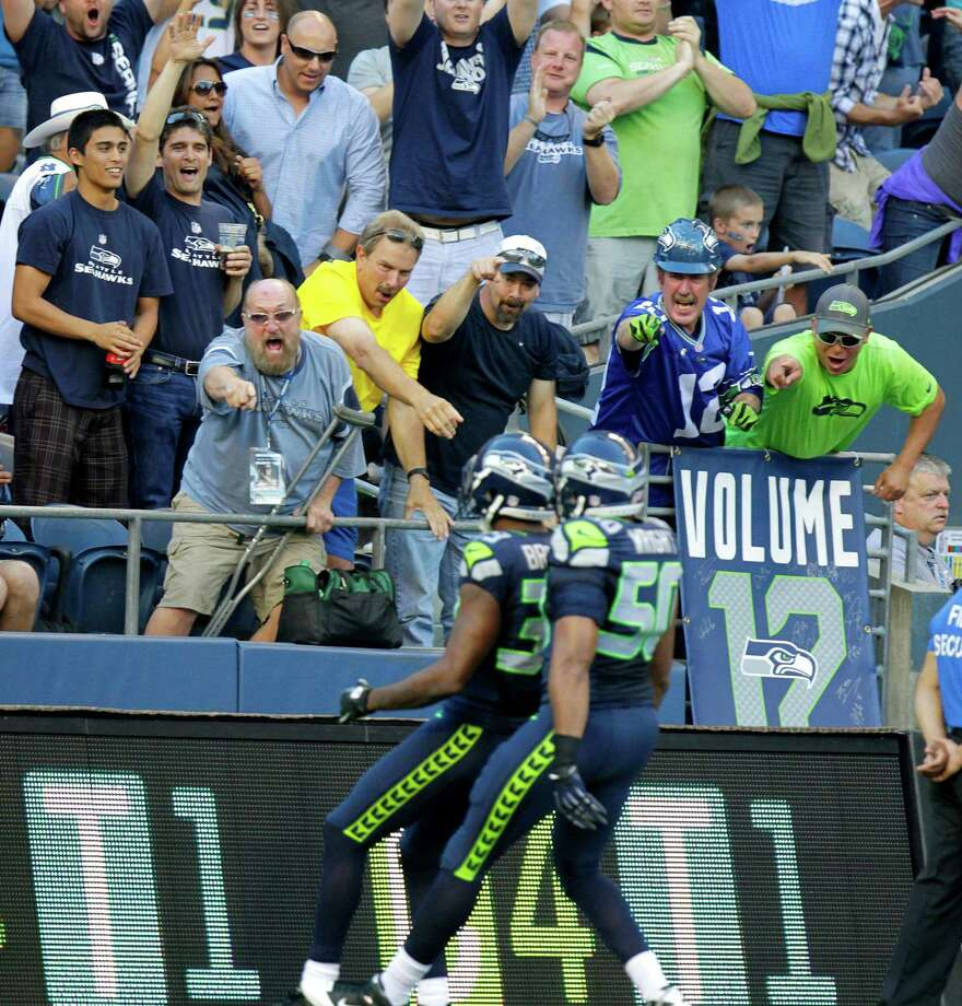 Fans celebrate in front Seattle Seahawks' Brandon Browner, left, and  K.J. Wright after Browner scored a touchdown on an interception in the first half Saturday. Photo: Ap