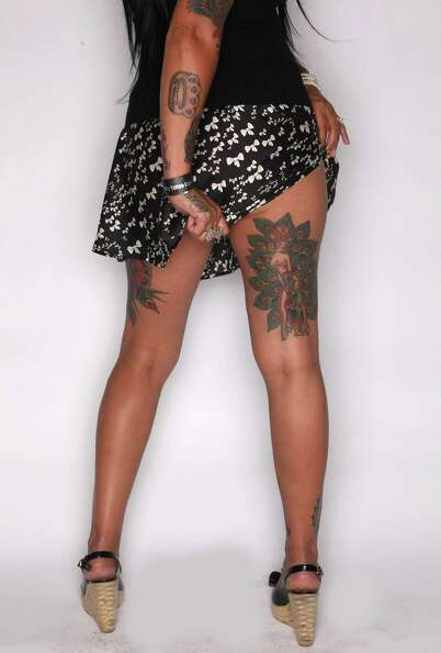 Krissy Logan of Portland shows her leg tattoos at the Seattle Tattoo Expo on Saturday.