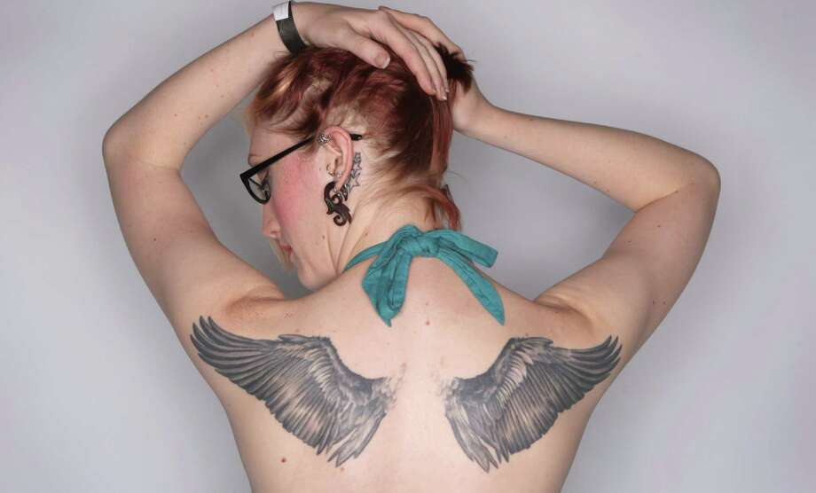 Erin Bohlmann of Seattle shows her wings at the Seattle Tattoo Expo. Photo: JOSHUA TRUJILLO / SEATTLEPI.COM