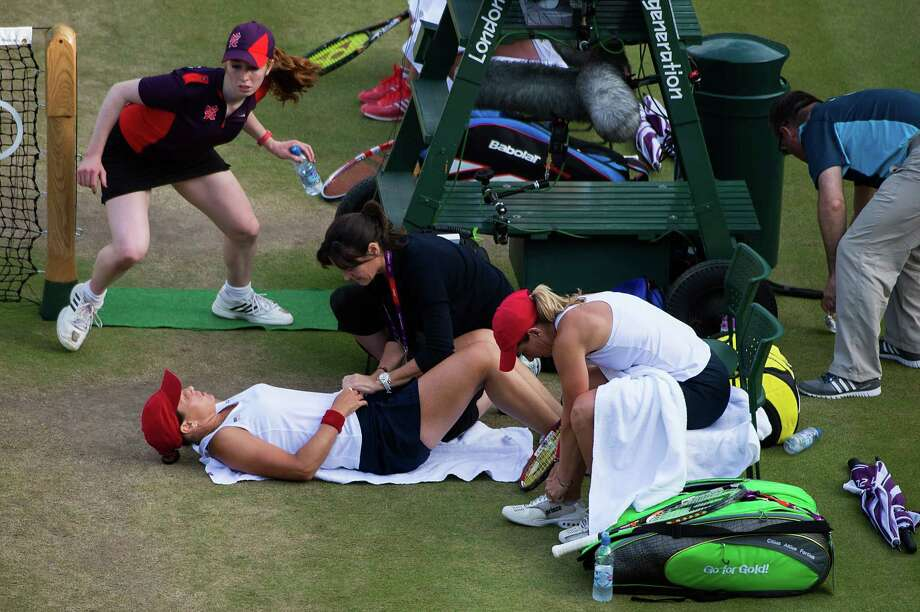 Liezel Huber receives treatment during the bronze-medal match in women's doubles. Huber and Lisa Raymond lost the match. Photo: Smiley N. Pool / © 2012  Houston Chronicle