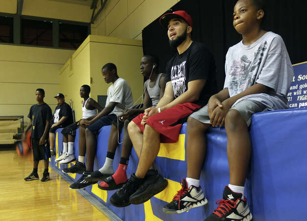 More than Champions Sports' youth camp founder David Josiah (second from right) sits with some of the campers to watch a game of basketball at Castle Hills First Baptist Church on Saturday, August 11, 2012. Josiah and his departed friend Josue Barea-Torres had a desire to start such a camp before Barea-Torres was gunned down in 2010. Spurred partially in honor of his friend, Josiah has helped the camp come to life and the organization opened a three-day camp for at-risk youth for the first time earlier this week. The camp reaches out to youth who have a desire to learn the game of basketball but the camp also attempts to teach life skills for their times off the court. The camp - which was free for the kids - concluded on Saturday. Photo: Kin Man Hui, SAN ANTONIO EXPRESS-NEWS / ©2012 San Antonio Express-News