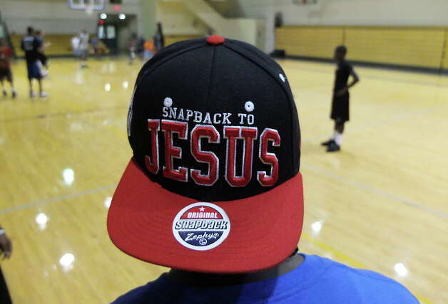 "More than Champions Sports' coach and mentor Jermaine Bell sports a ball cap with the saying, ""Snapback to Jesus,"" while watching a three-on-three game of basketball at Castle Hills First Baptist Church on Saturday, August 11, 2012. Organizer and founder David Josiah and his departed friend Josue Barea-Torres had a desire to start a camp for at-risk youth before Barea-Torres was gunned down in 2010. Spurred partially in honor of his friend, Josiah has helped the camp come to life and the organization opened a three-day camp for at-risk youth for the first time earlier this week. The camp reaches out to youth who have a desire to learn the game of basketball but the camp also attempts to teach life skills for their times off the court. The camp - which was free for the kids - concluded on Saturday. Photo: Kin Man Hui, SAN ANTONIO EXPRESS-NEWS / ©2012 San Antonio Express-News"