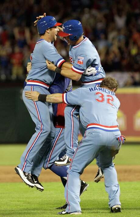 Rangers rookie Mike Olt, left, celebrates with teammates Michael Young and Josh Hamilton after Olt's walk-off, game-winning RBI single. Photo: LM Otero / AP
