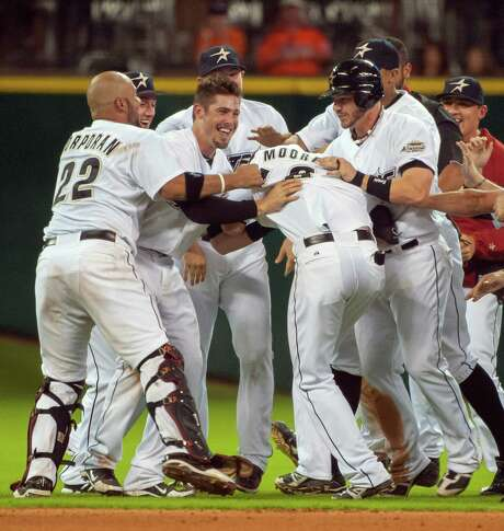 Scott Moore, center, is no match for his jubilant teammates, who are in a mood to celebrate after Moore's single in the 10th inning drove in the winning run. Photo: Dave Einsel / FR43584 AP