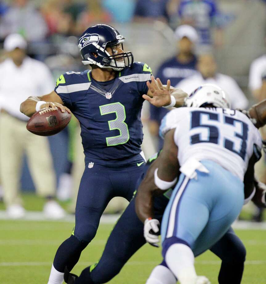 Seattle Seahawks quarterback Russell Wilson  throws a touchdown pass as Tennessee Titans linebacker Zac Diles puts on defensive pressure in the second half Saturdaye. Photo: Ap