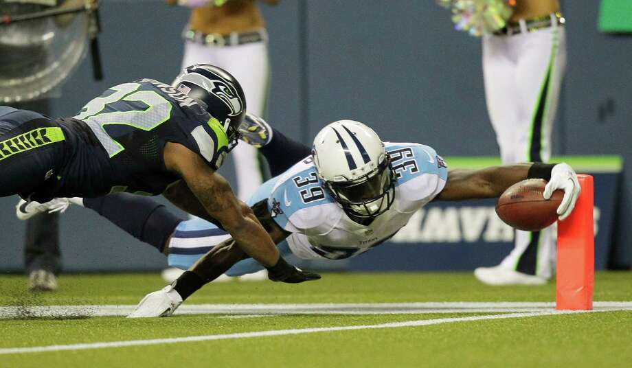 Tennessee Titans'  Darius Reynaud dives in for a touchdown past Seattle Seahawks'  Jeron Johnson, left, after returning a punt for 85 yards in the second half Saturdaye. Photo: Ap