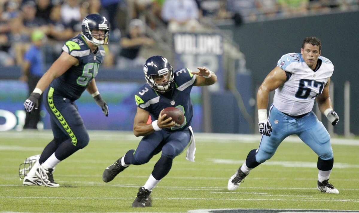 Seattle Seahawks quarterback Russell Wilson in action with J.R. Sweezy (64) and Tennessee Titans defensive tackle Mike Martin .