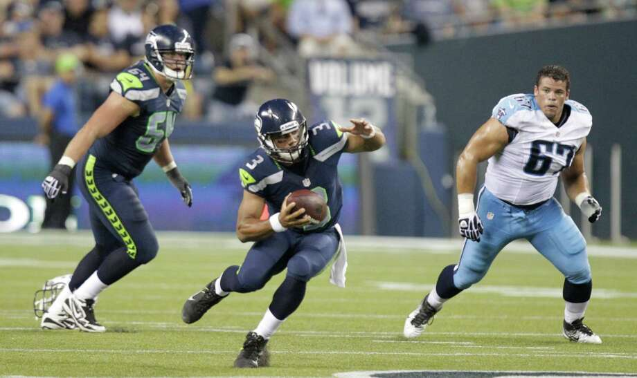 Seattle Seahawks quarterback Russell Wilson in action with J.R. Sweezy (64) and Tennessee Titans defensive tackle Mike Martin . Photo: Ap