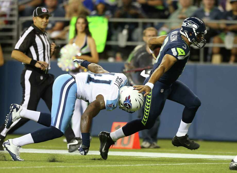 Russell Wilson scores a touchdown against Christian Scott of the Tennessee Titans on Saturday. Photo: Otto Greule Jr, Getty