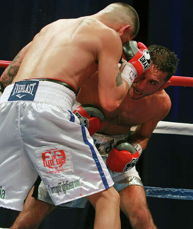 Brian Vera (left) pounds on Sergio Mora in the main event at the Alamodome on August 11, 2012. Photo: Tom Reel, San Antonio Express-News / ©2012 San Antono Express-News