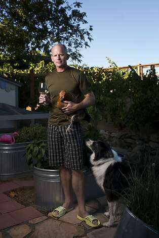 Winemaker-buyer Jim Denham with his dog and a chicken from his coop. Photo: Jason Henry, Special To The Chronicle