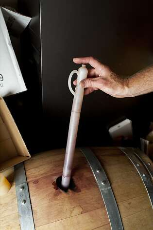 Denham siphons homemade wine aging in his home. Photo: Jason Henry, Special To The Chronicle
