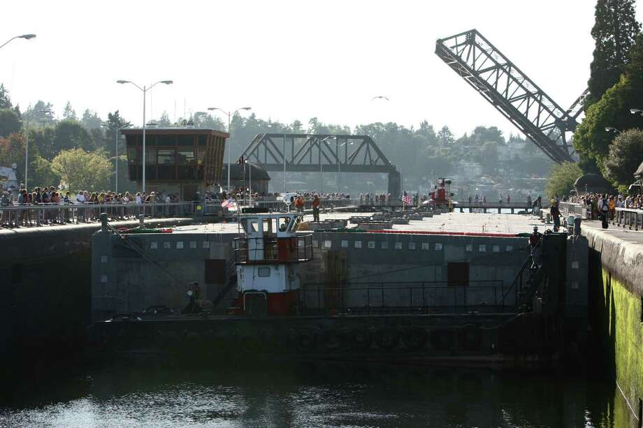 Tugs manuever as the first of the new 520 bridge pontoons is squeezed through the Ballard Locks as it makes its way to Lake Washington on Saturday, August 11, 2012. The pontoon was constructed in Grays Harbor and moved with tugboats to Seattle. It is the first of 77 pontoons of different sizes that will be used to build the floating span across Lake Washington. Photo: JOSHUA TRUJILLO / SEATTLEPI.COM