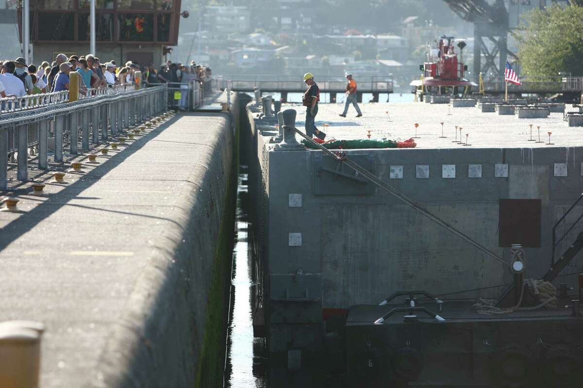Workers watch carefully as the first of the new 520 bridge pontoons is squeezed through the Ballard Locks.