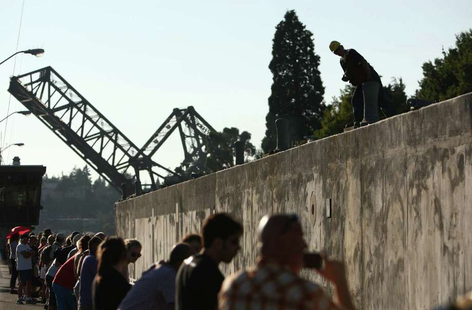 Workers watch carefully as the first of the new 520 bridge pontoons is squeezed through the Ballard Locks. Photo: JOSHUA TRUJILLO / SEATTLEPI.COM
