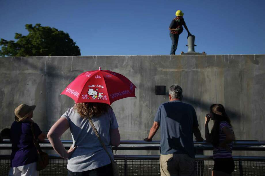 Spectators watch as the first of the new 520 bridge pontoons is squeezed through the Ballard Locks as it makes its way to Lake Washington. Photo: JOSHUA TRUJILLO / SEATTLEPI.COM