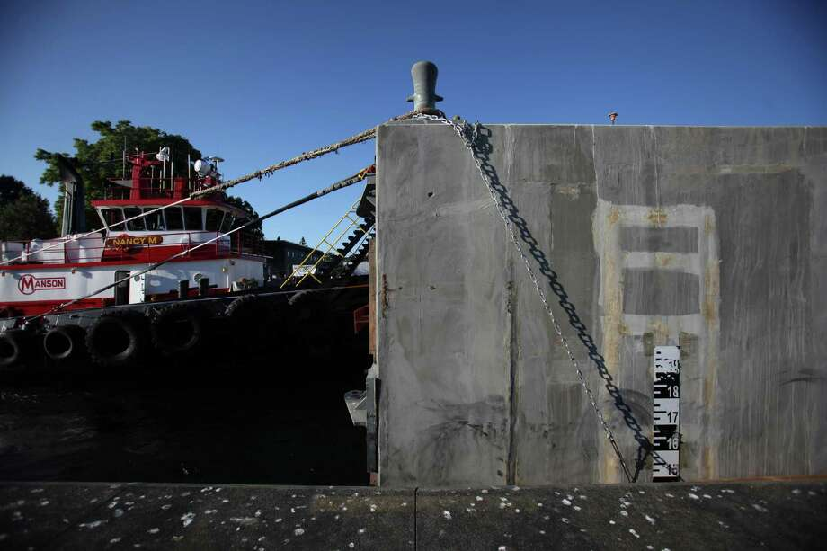 A tug pushes the first of the new 520 bridge pontoons through the Ballard Locks. Photo: JOSHUA TRUJILLO / SEATTLEPI.COM