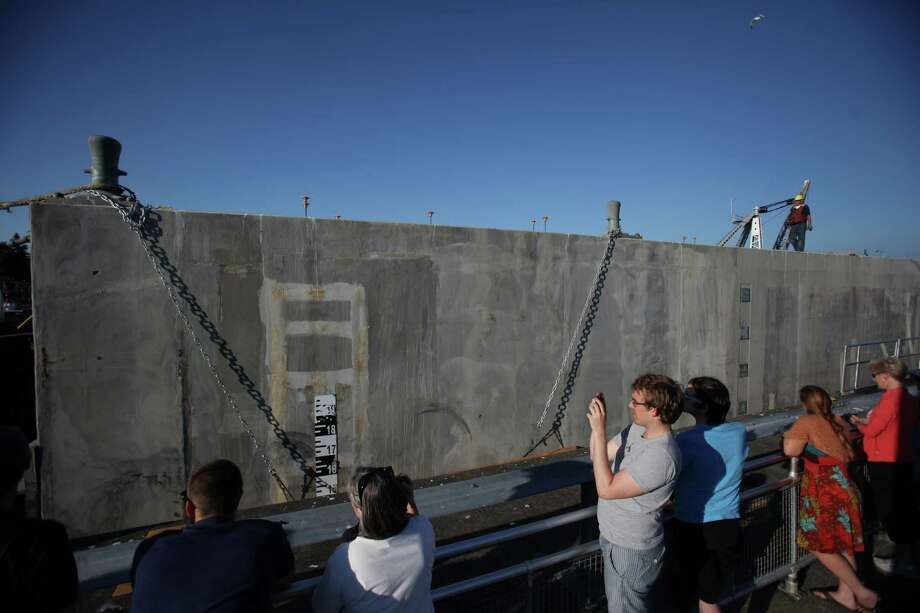 Spectators watch as the first of the new 520 bridge pontoons is squeezed through the Ballard Locks. Photo: JOSHUA TRUJILLO / SEATTLEPI.COM