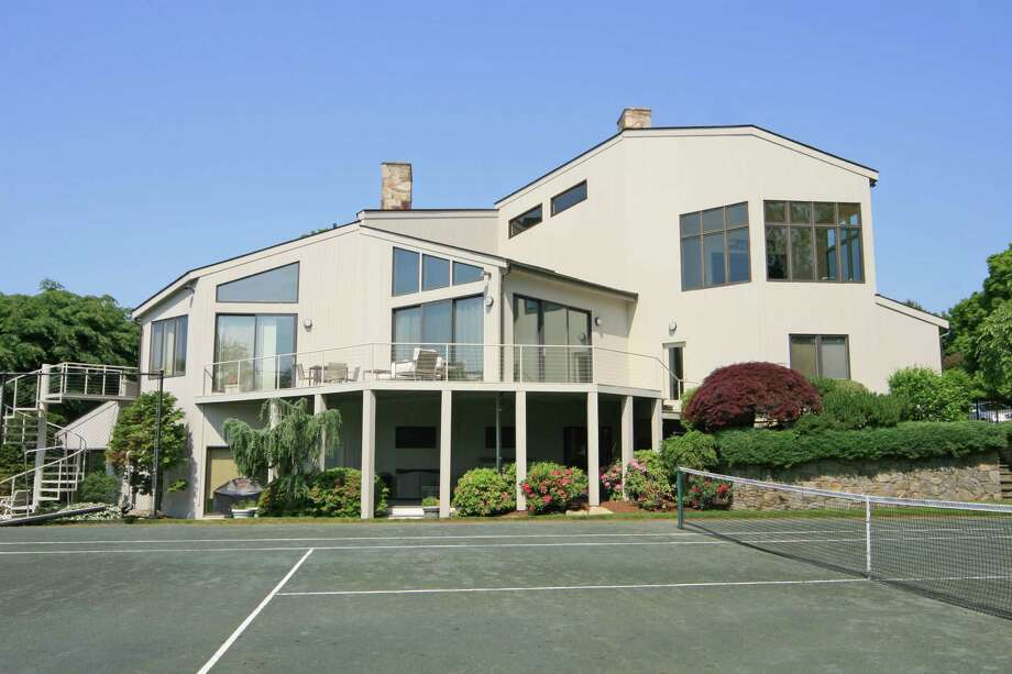 This contemporary home on Harbor Hill, as seen from its tennis court, was built in 1989 on just over an acre of land. The property's other recreational features include an out-door, in-ground swimming pool and a gym and a media room inside the 5,000-square-foot house. Photo: Contributed Photo