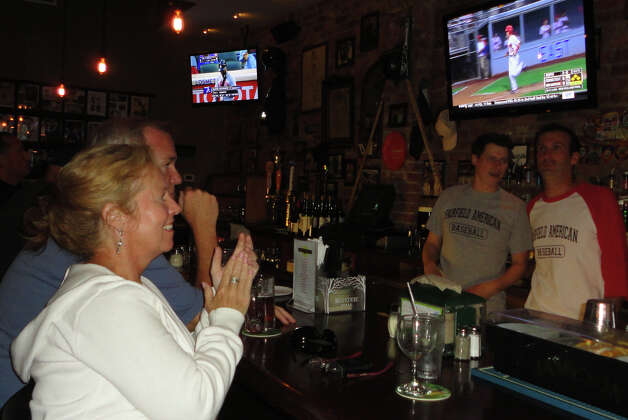 Maureen Martin and her husband John sit at the bar of Colony Grill on Saturday evening watching Fairfield American Little League team win the New England regional championship. Photo: Meg Barone / Fairfield Citizen freelance