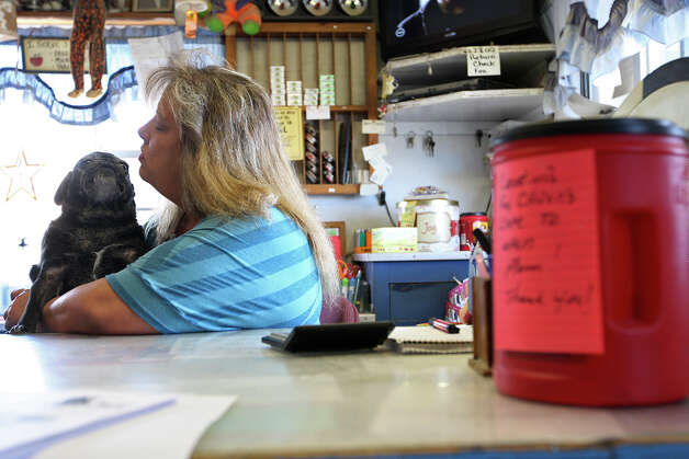 "Caren Calloway, 47, plays with Snoopy while working at a small convenience store in Mentone, Texas, Wednesday, July 25, 2012. The store is the only business in Loving County and is located 130 miles west of Midland, Texas. With constant traffic from the oil and gas business she said, ""It's crazy. It used to be you could pull out of the store and there would be no traffic for miles. Now you're gonna get hit if you don't look both ways twice."" The coffee can to the right is for donations to help her open a cafe across the street from the store. It�ll serve locals and oil field workers. ""Everybody's got to eat,"" she said. Photo: Jerry Lara, Jerry Lara/Express-News / © 2012 San Antonio Express-News"