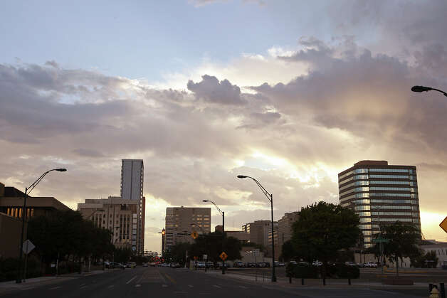The sun sets behind the Midland, Texas skyline, Wednesday, July 25, 2012. The oil and gas boom in the Permian Basin is approaching a million barrels a day and with gas production, brings $2.5 to $3 billion in revenues monthly. With the boom, the population of the Midland-Odessa metro area is expected to double from 200,000 to 400,000 in the coming years. Photo: Jerry Lara, Jerry Lara/Express-News / © 2012 San Antonio Express-News
