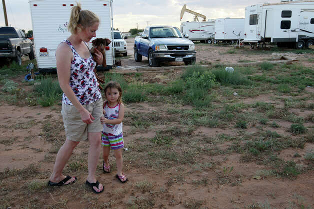 "Christie Davis, 36, walks with her daughter, Ruby, 3, while carrying ""Brownie"" at a RV park in Midland, Texas, Wednesday, July 25, 2012. Her husband, who works in the weatherization business, couldn't find housing that was affordable in the area due to high demand from workers in the oil and gas industry. Photo: Jerry Lara, Jerry Lara/Express-News / © 2012 San Antonio Express-News"