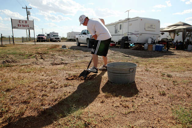 Brandon Robertson, 15, prepares to fill a tub with dirt while planting a cactus for his mother at the E&D RV Park near Stanton, Texas, Wednesday, July 25, 2012. Robertson's father is vacuum truck driver in the oil and gas industry. They are from Merkel, a small town 130 miles up Interstate 20. Before buying a FEMA trailer from East Texas and moving to the park, Bryan Robertson drove two hours each way because he couldn't find a place to stay in Midland. Living in primitive conditions, the young Robertson said, �I hate it, there�s nothing to do here. I want to get out and do things, but I don�t drive. But I�d rather be here than somewhere else and be completely broke.� Photo: Jerry Lara, Jerry Lara/Express-News / © 2012 San Antonio Express-News
