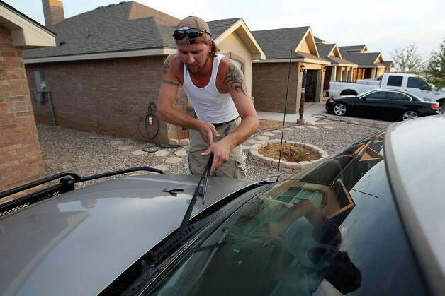 Electrician Josh Busick, 30, changes the wipers on his pickup truck at  Legends Park subdivision in Midland, Texas, Tuesday, July 24, 2012. According to Betenbough Homes spokesperson, Jeanna Roach, houses start in the $140,000's and for the past 9-12 months, the waiting list has not gone under 100 buyers. The company starts construction on 20 new homes a month and the phase will top out at 500 homes. Photo: Jerry Lara, Jerry Lara/Express-News / © 2012 San Antonio Express-News
