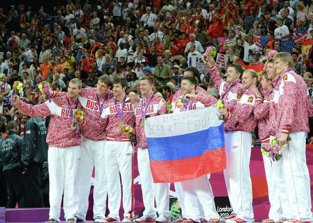 Russian players pose on the podium after winning the bronze medal in the London 2012 Olympic Games men's basketball competition at the North Greenwich Arena in London on August 12, 2012. The US won the gold medal followed by the silver to Spain and the bronze to Russia. AFP PHOTO /MARK RALSTONMARK RALSTON/AFP/GettyImages Photo: MARK RALSTON, AFP/Getty Images / AFP