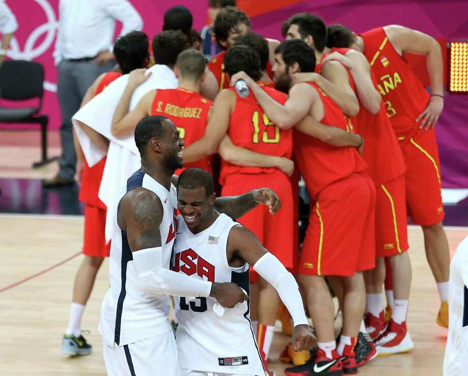LONDON, ENGLAND - AUGUST 12:  LeBron James #6 of the United States and team mate Chris Paul #13 of the United States celebrate winning the Men's Basketball gold medal game between the United States and Spain as Spain form a huddle on Day 16 of the London 2012 Olympics Games at North Greenwich Arena on August 12, 2012 in London, England. The United States won the match 107-100. Photo: Streeter Lecka, Getty Images / 2012 Getty Images