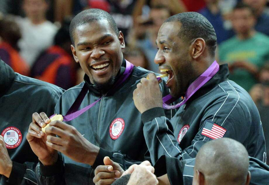 US players pose on the podium after winning the gold medal in the London 2012 Olympic Games men's basketball competition at the North Greenwich Arena in London on August 12, 2012. The US won the gold medal followed by the silver to Spain and the bronze to Russia. AFP PHOTO /MARK RALSTONMARK RALSTON/AFP/GettyImages Photo: MARK RALSTON, AFP/Getty Images / AFP