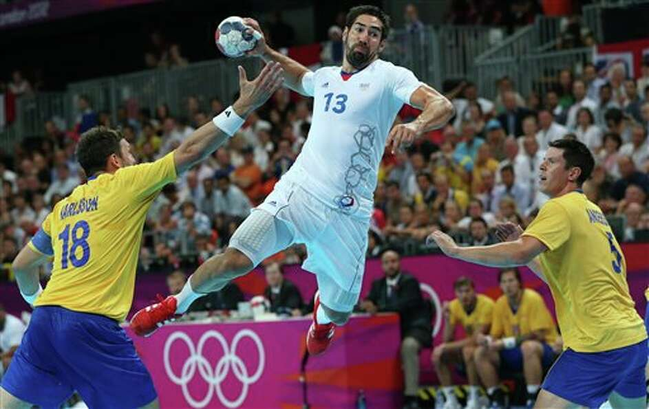 France's Nikola Karabatic, center, leaps in the air to score past Sweden's Tobias Karlsson, left, an