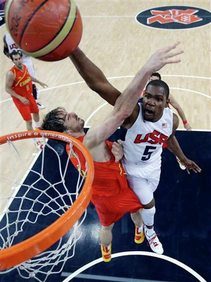 United States' Kevin Durant (5) slam dunks to score over Spain's Pau Gasol, left, during the men's gold medal basketball game at the 2012 Summer Olympics, Sunday, Aug. 12, 2012, in London. Photo: AP