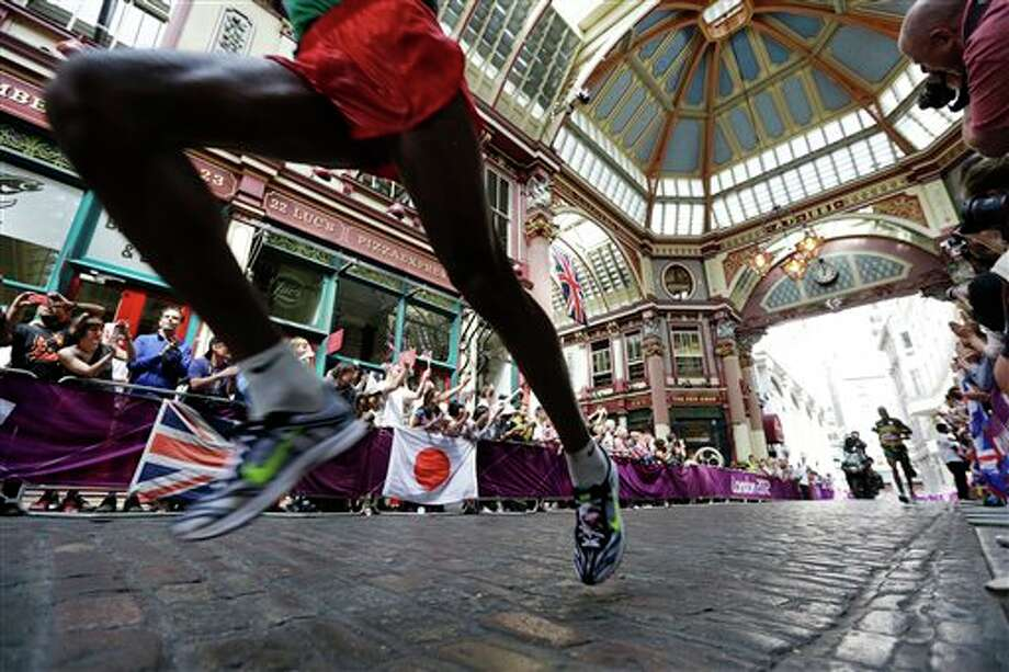 Athletes run through the Leadenhall Market during the men's marathon at the 2012 Summer Olympics, Sunday, Aug. 12, 2012, in London. Photo: AP