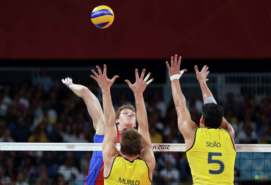 Dmitriy Muserskiy #13 of Russia goes up for a shot against Murilo Endres #8 and Sidnei Dos Santos Junior #5 of Brazil during the Men's Volleyball gold medal match. Photo: Elsa, Getty Images / 2012 Getty Images