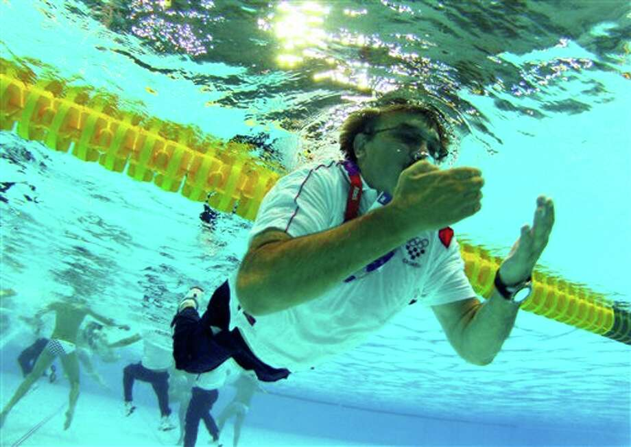 Croatia coach Ratko Rudic swims after jumping in the pool to celebrate his team's 8-6 victory over Italy during the men's water polo gold medal match at the 2012 Summer Olympics, Sunday, Aug. 12, 2012, in London. Photo: AP